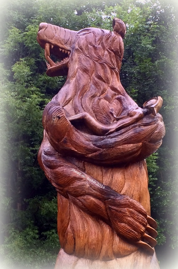 "Enormous carving by a local artist of a bear holding one of ""the beautiful girls"""